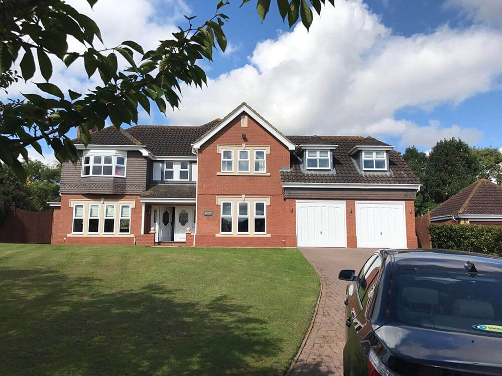 Exterior of Home with an open white UPVC front door and a drive way