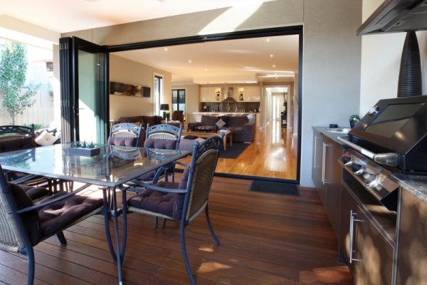 Black framed bi-fold doors to patio with BBQ & dining tbble