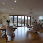 An open plan living and dining room featuring closed bifold doors, with wooden frames, looking out onto the garden.