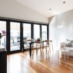 Modern, closed bifold doors with black frames looking out onto a balcony