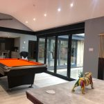 Closed contemporary bifold doors with a black frame, fitted in a modern home, featuring a pool table.