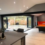 Sleek, black framed bifold doors installed on a corner in a home.