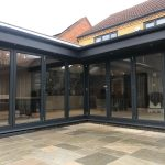 Closed bifold doors with a dark grey frame, seen from a paved patio in a garden.