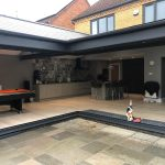 Two sets of open bifold doors, installed at a right angle, opening into the kitchen of a home.